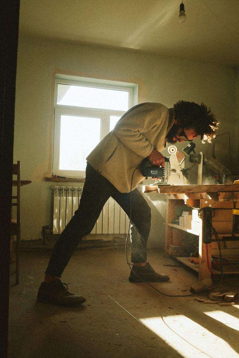 Kirill sanding a piece of wood in his studio
