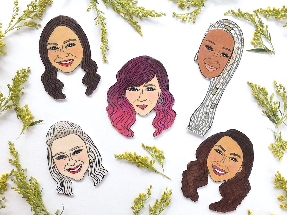 Five custom-drawn face magnets on a white surface with flowers.