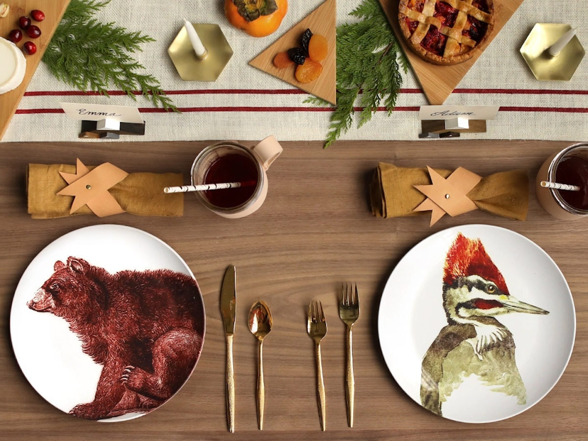 A festive woodland-themed tablescape set with animal plates.