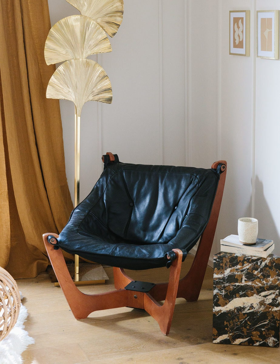 A black leather sling chair sits next to a gold ginkgo leaf lamp and a stone side table with books and a coffee cup on top.