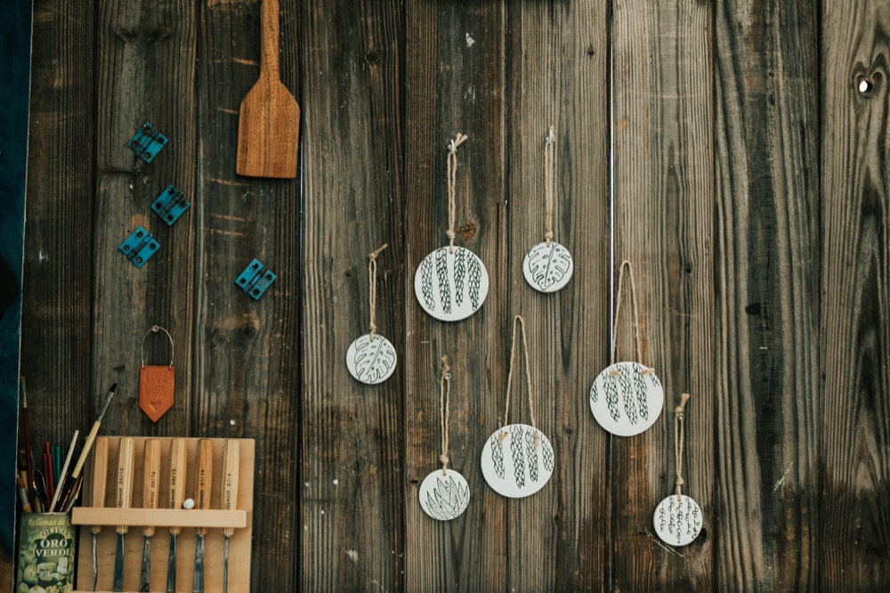 A set of Sally's ceramic, botanical-inspired ornaments hanging on a wall outdoors