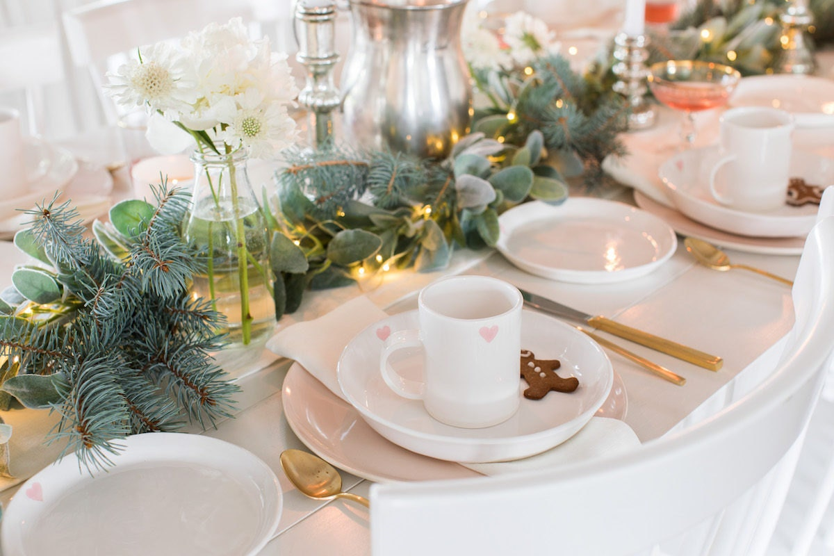 Holiday tabletop decorated with mixed greenery including eucalyptus and spruce