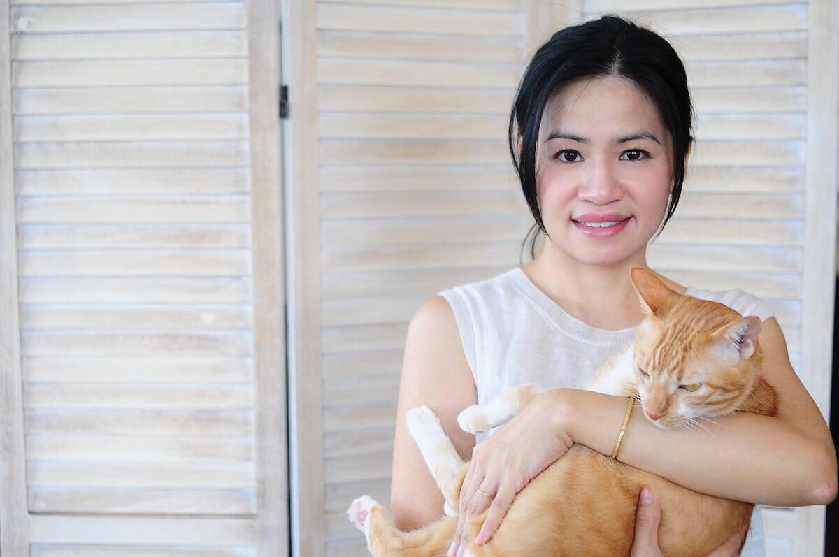 Designer Joe Wong of Artemis Leatherware holding her cat, Yoshi