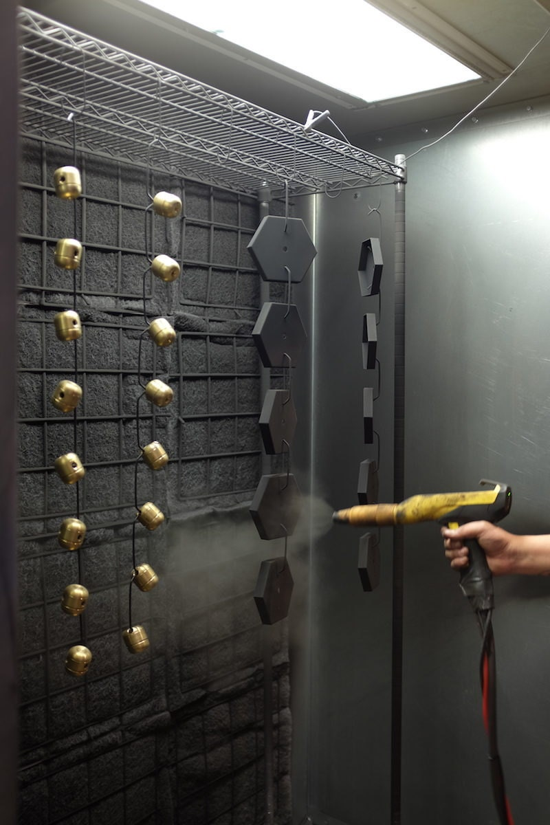 Kyle sprays the finish onto a string of brass lighting components
