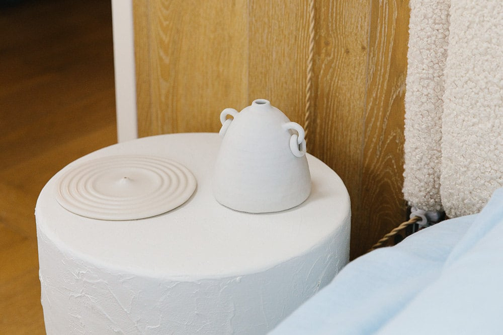 A cream-colored rippled incense holder and a matte ceramic vase rest atop a white plaster side table.