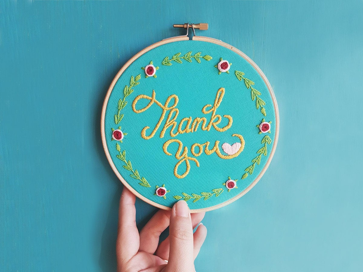 An embroidery hoop stitched with the words