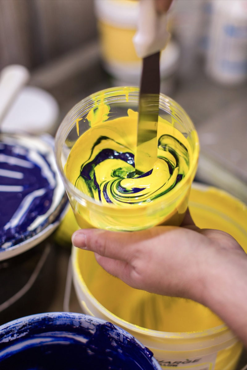 Mixing yellow and blue paints to create a specific shade for screenprinting.