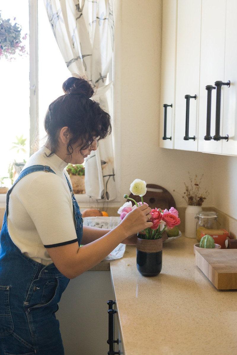 Melanie arranges flowers from the farmer's market in her kitchen