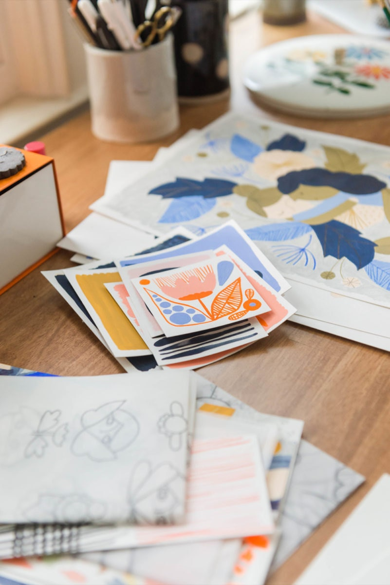 Assorted cards and illustrated prints stacked on Meenal's desk