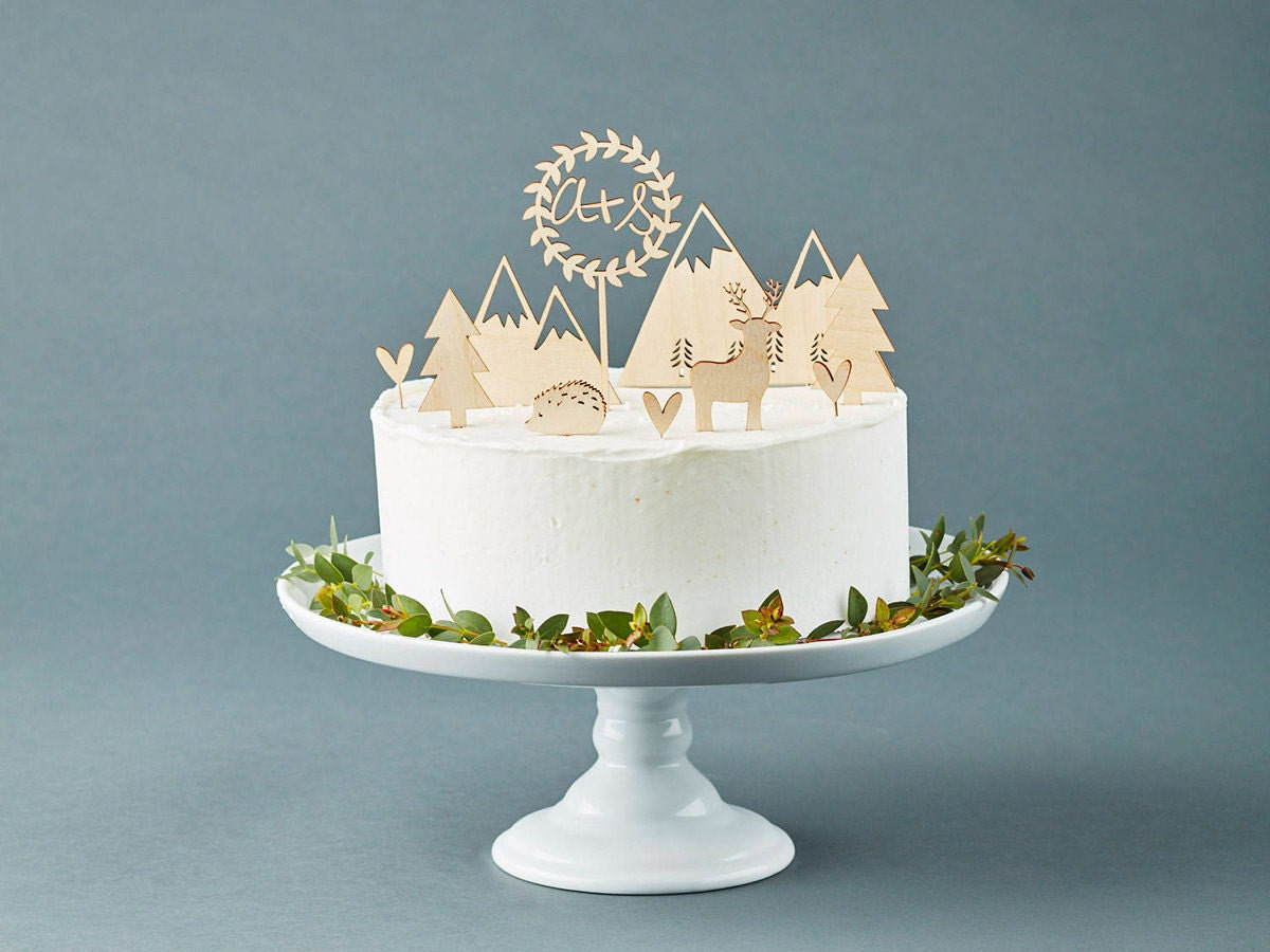 Rustic wooden laser cut cake toppers from Light + Paper displayed on a white wedding cake