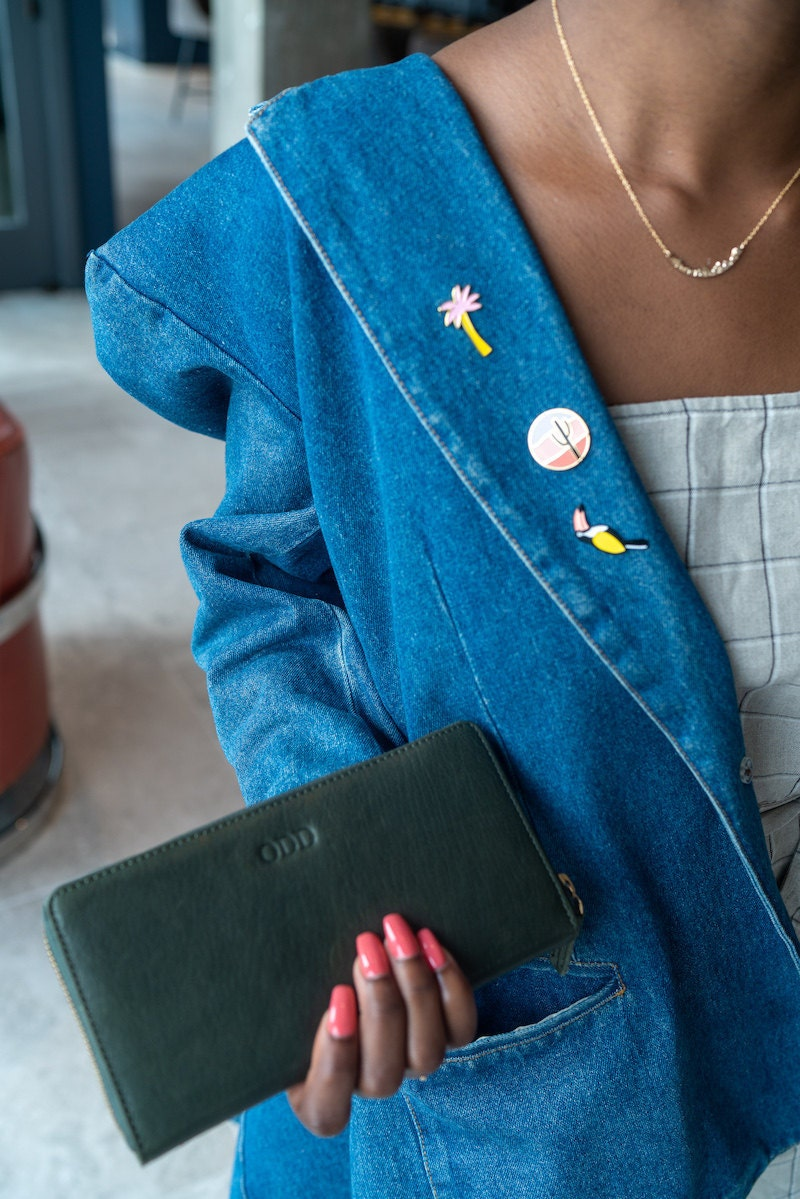 Sofi models a personalized leather wallet and colorful enamel pins from Etsy
