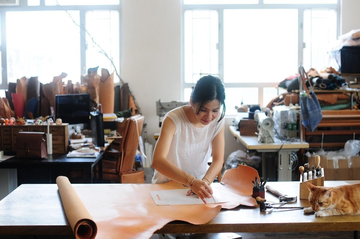 Joe measuring leather in her studio