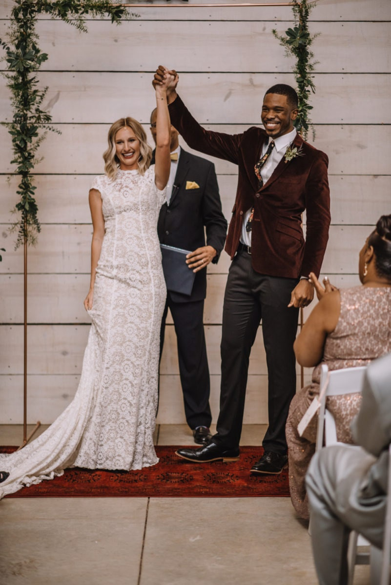 Emily and Terrell raise their hands in celebration of their I-dos