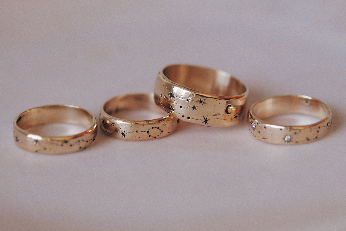 A collection of gold ring bands hand-engraved with constellations from Sofia Zakia