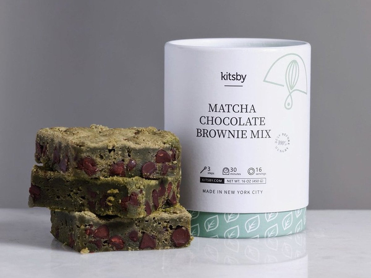 Three matcha chocolate brownies next to a package of the mix to make them.