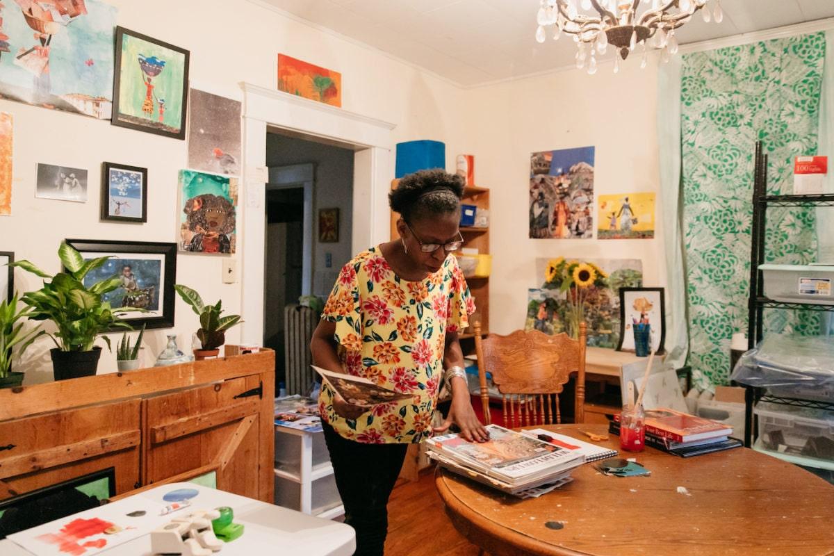 Mirlande sorts through magazines in her Baltimore dining room studio