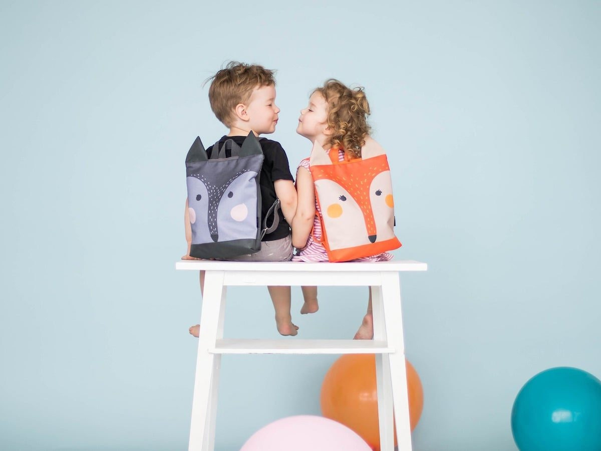 Two children wearing wolf and fox backpacks from MUNI