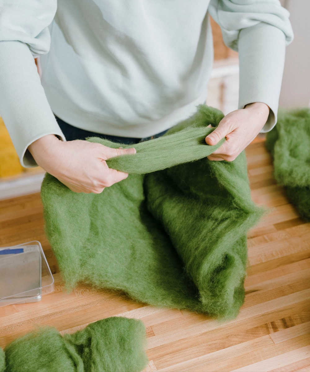 Elizabeth creating a skein of green wool.