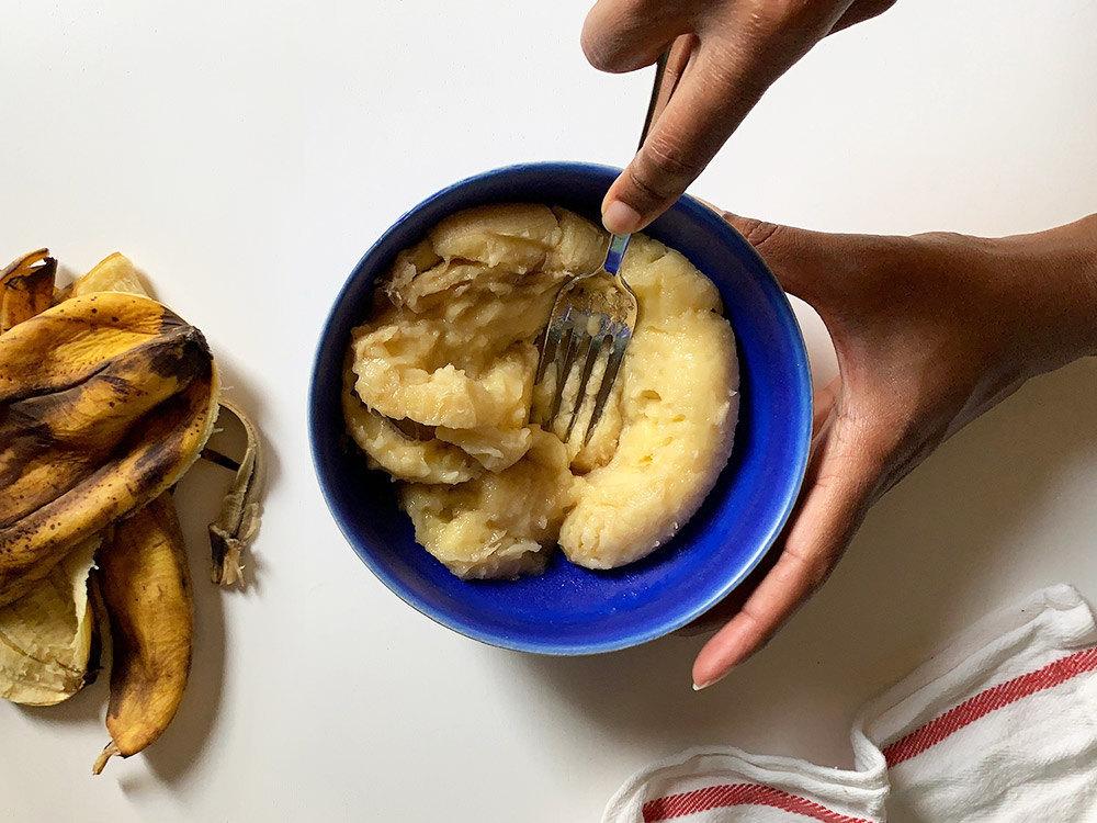 Aravis mashing bananas with a fork.