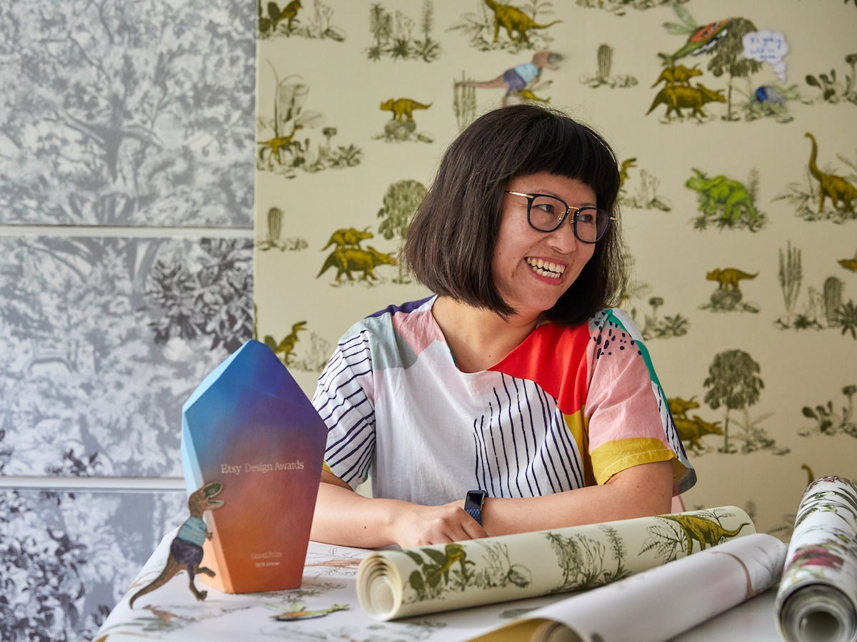 Portrait of Etsy Design Awards Grand Prize Winner Sian Zeng in front of her interactive magnetic dinosaur wallpaper