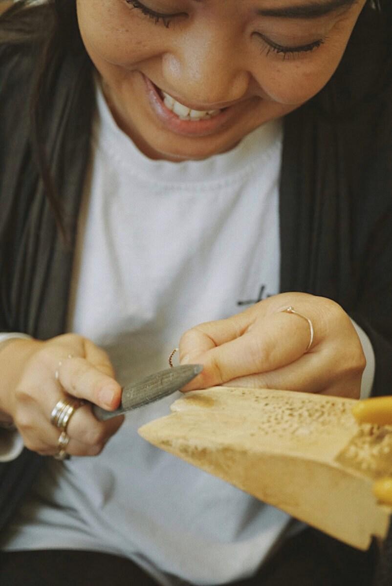 Katherine metalsmithing in her studio.