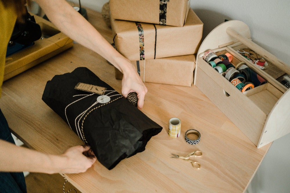 Eda wrapping an order for shipment