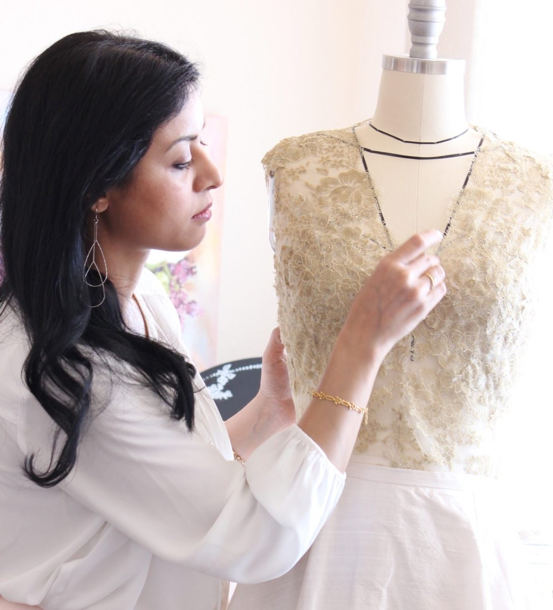 Smitha pins a gold lace bridal top on a form
