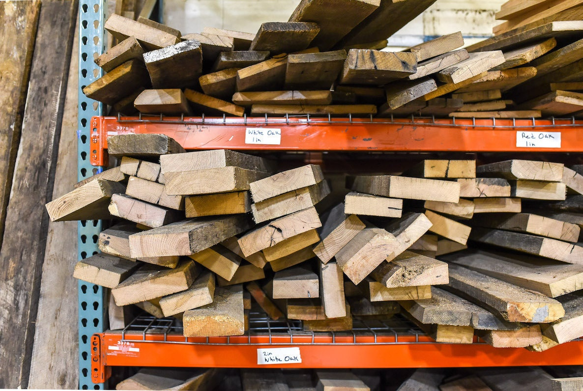 Wood grouped by type on shelves in the What WE Make workshop