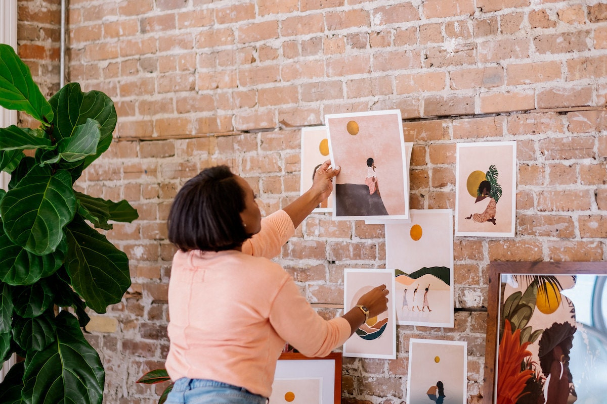 Melissa hanging prints on the wall of her studio