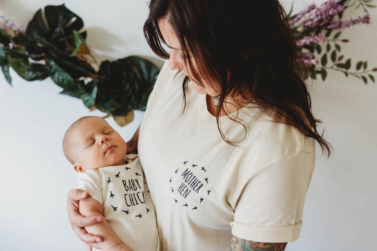 """A mother wearing a """"Mother Hen"""" T-shirt holds a baby wearing a """"Baby Chick"""" T-Shirt"""