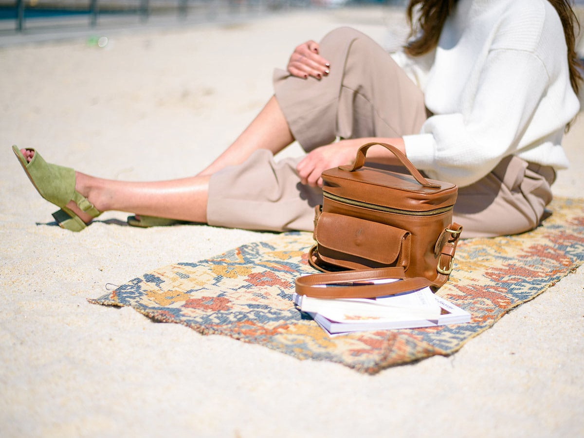 Woman sitting on a blanket with a Jolie Laide leather camera bag