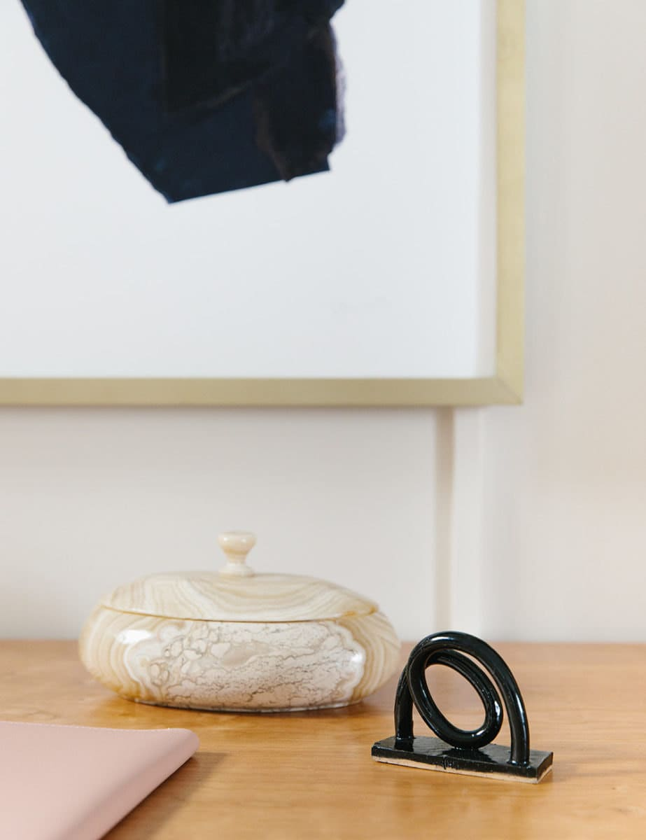 An onyx lidded dish and a swirly ceramic figurine sit atop a wooden desk.