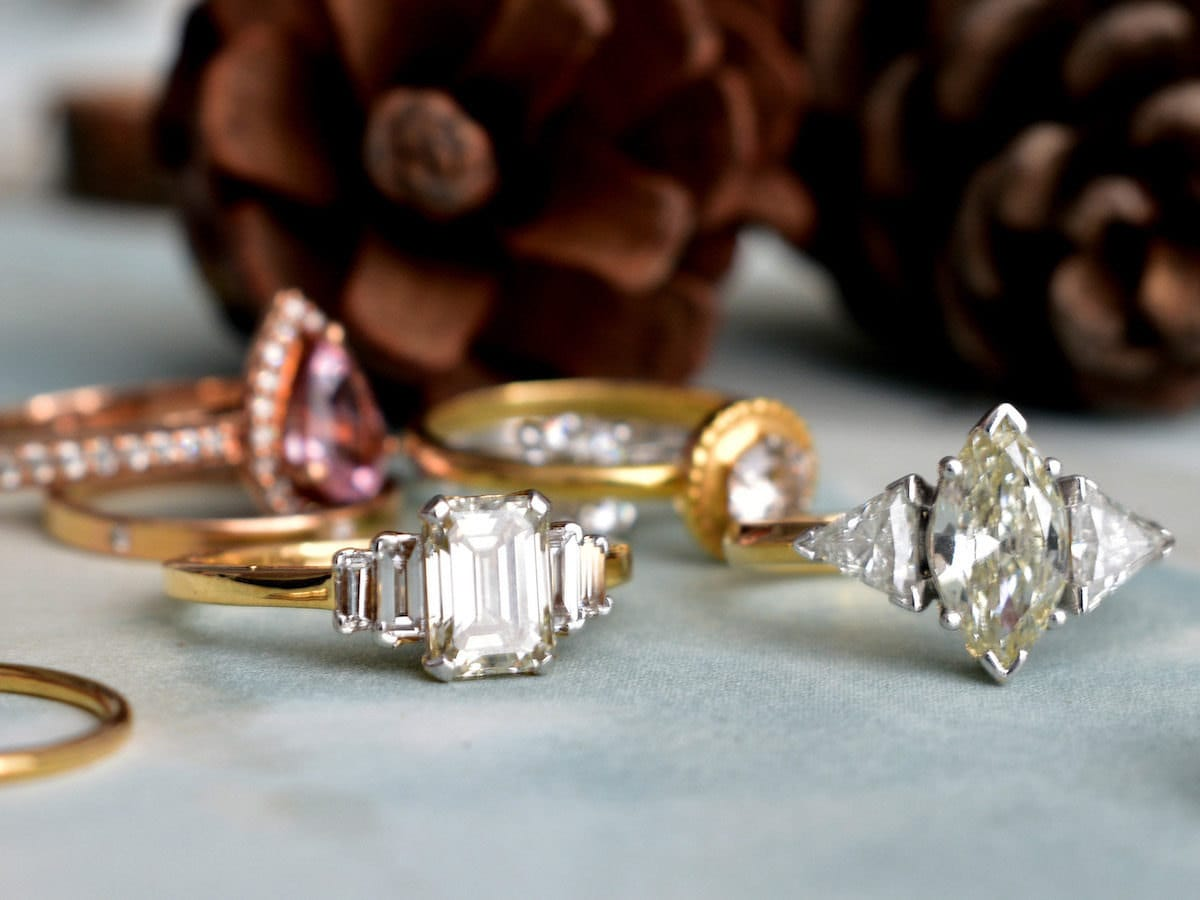 Four sparkling engagement rings displayed on a gray surface