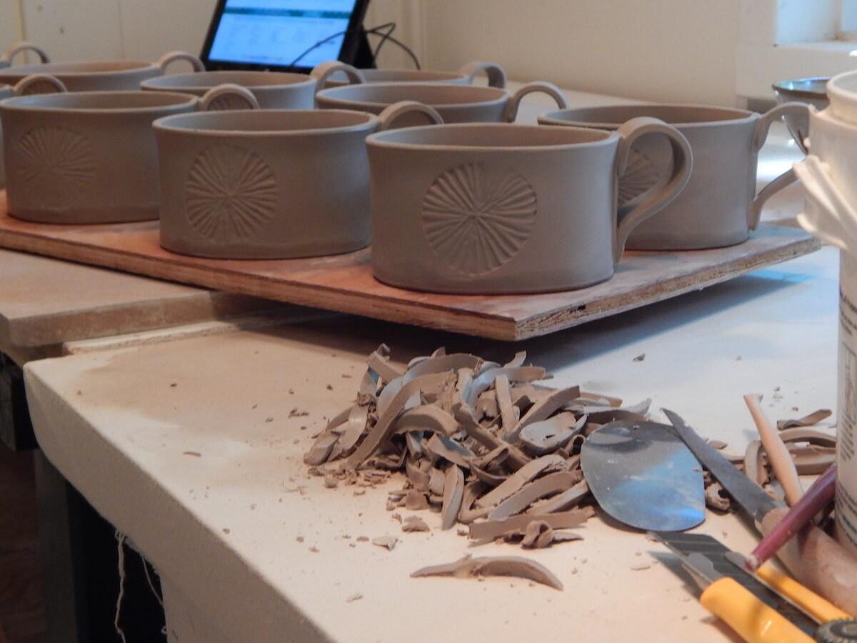 A fresh batch of sand dollar mugs await their firing in the kiln