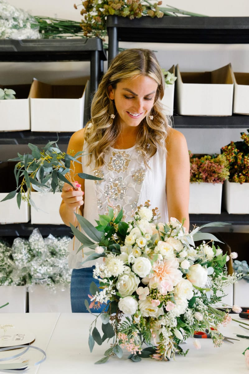 Brittany adds faux foliage to a big, white bouquet