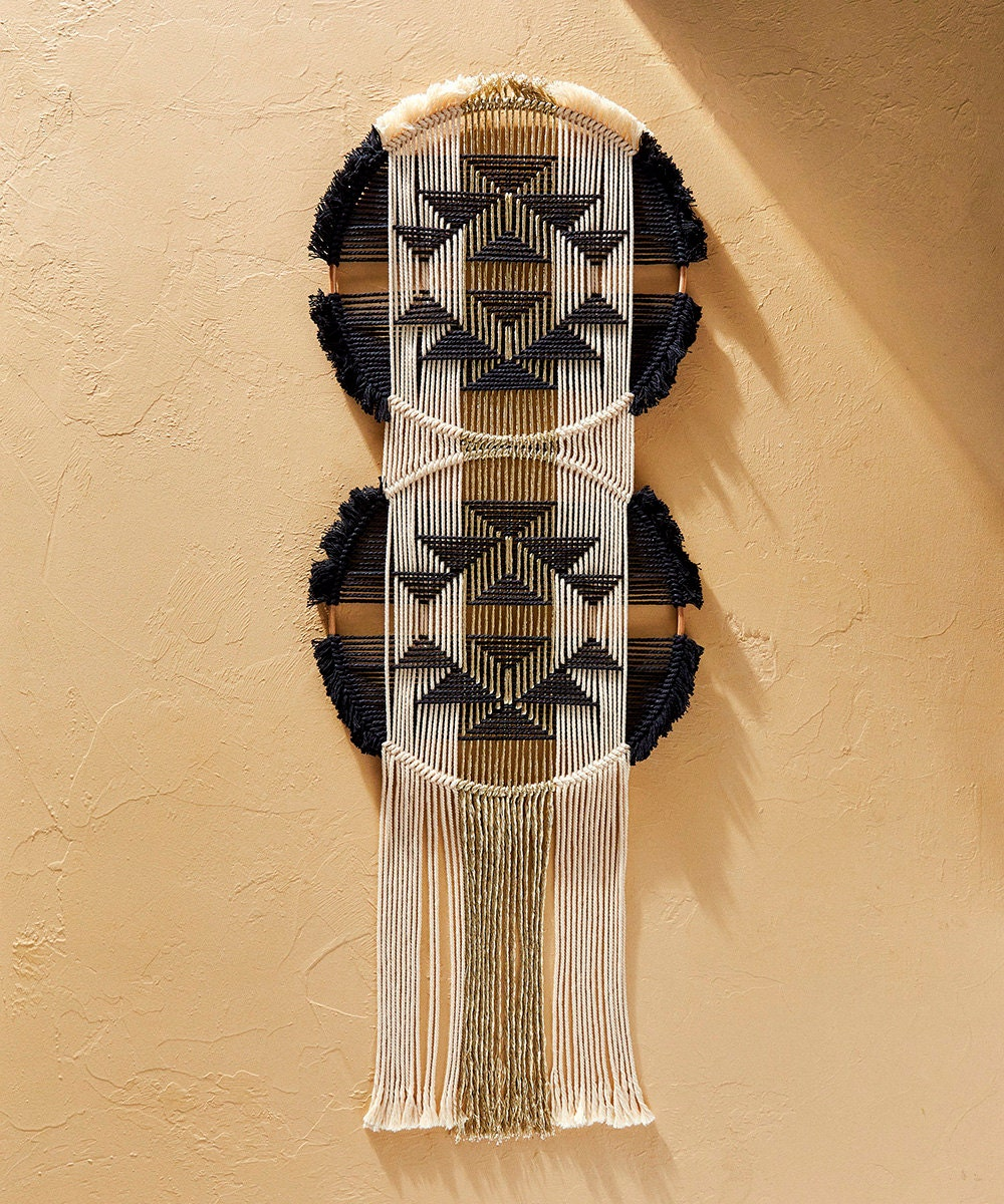 A black, white, and gold woven wall hanging.