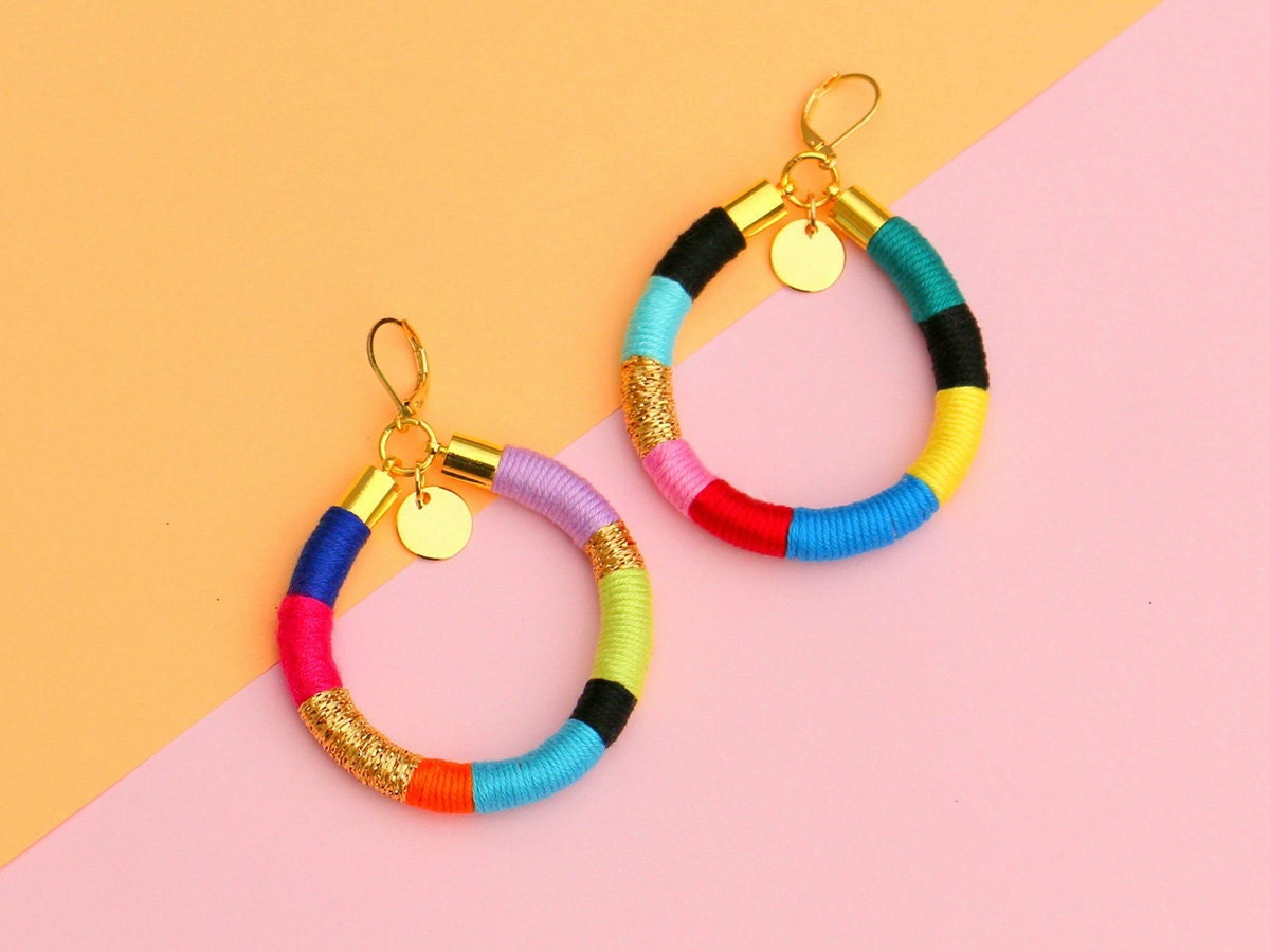 Colorful hoop earrings against a pink and orange background.