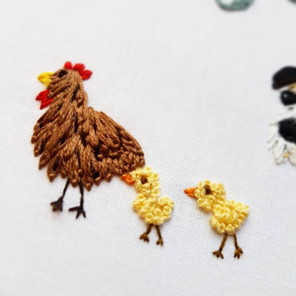 """Close up detail on an embroidered chicken and baby chicks from one of Natalie's """"new home"""" hoops."""