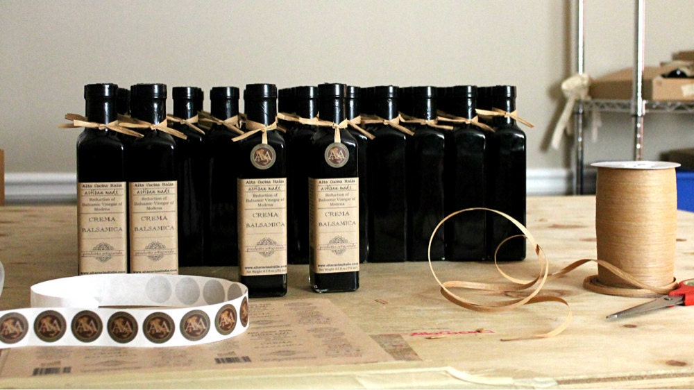 Bottles of balsamic getting labeled and ribboned
