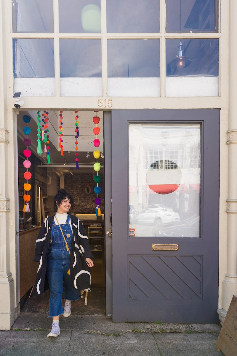 Melanie and Rover walk out the colorful front door of Oakland's Crown Nine boutique