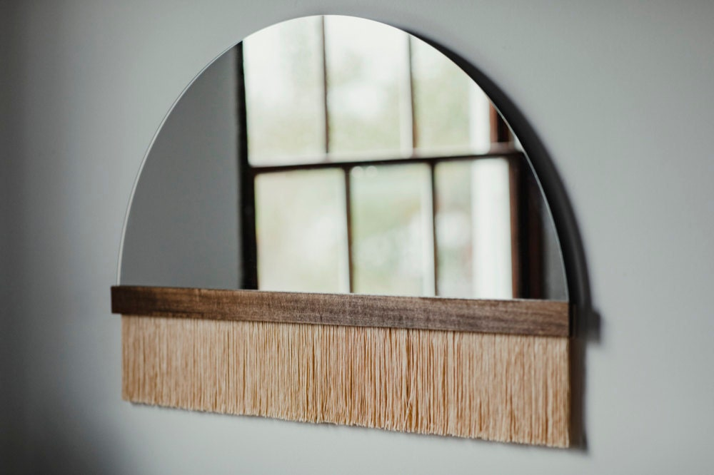 """A large """"Aria solo"""" fringe mirror with wood bar and peach dip-dyed fringe from Candice Luter."""