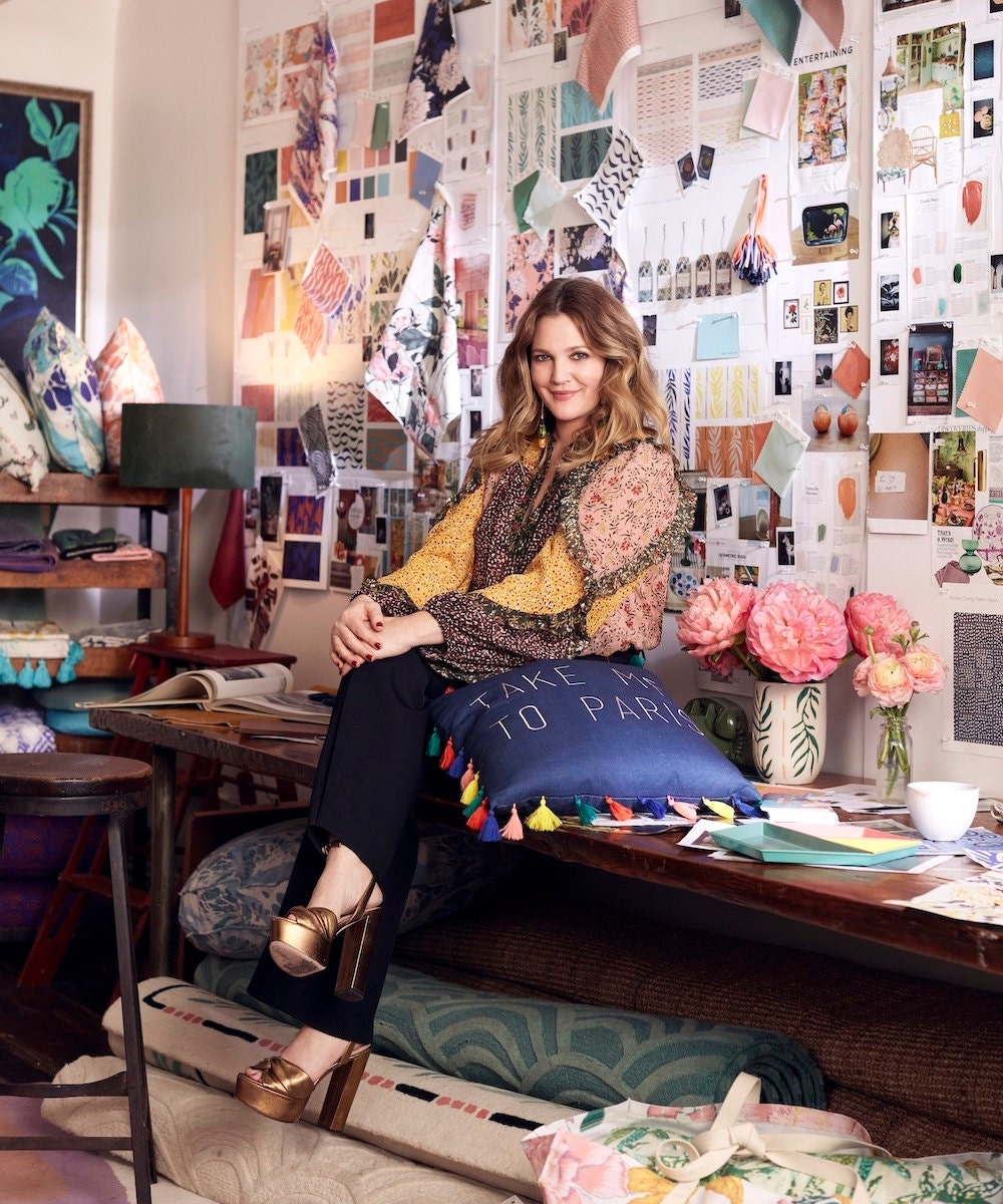 Portrait of Drew Barrymore in front of a fabric mood board.