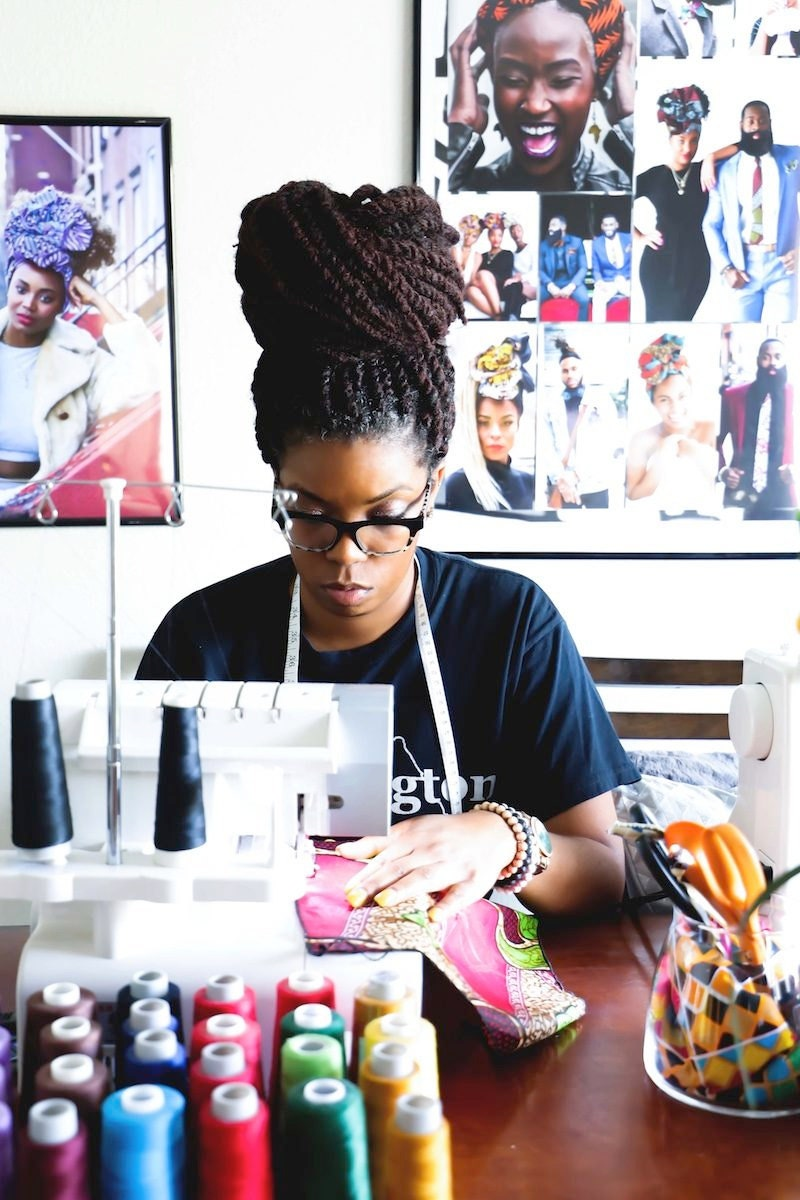 Ade sitting at her sewing machine in her studio