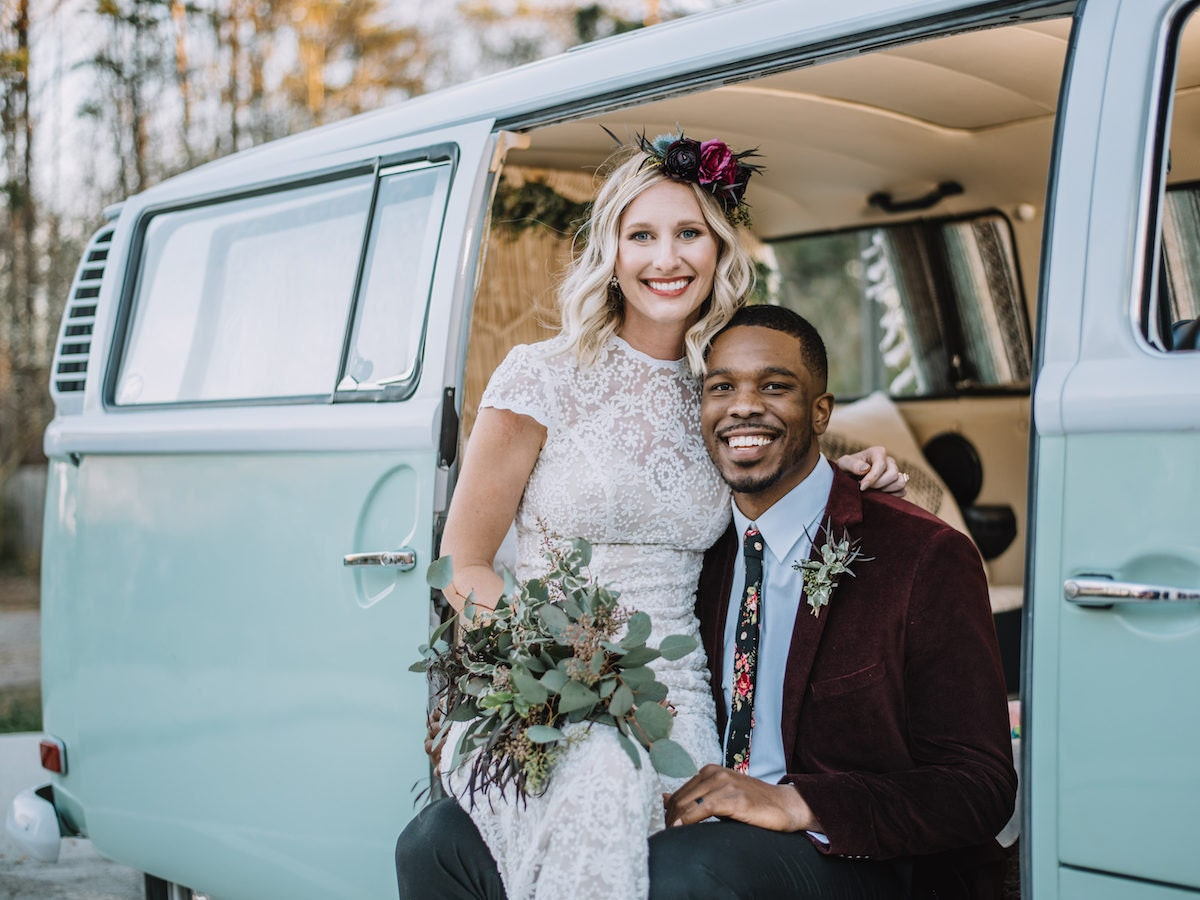 A bride and groom pose together in front of a blue Volkswagen van-turned photo booth.