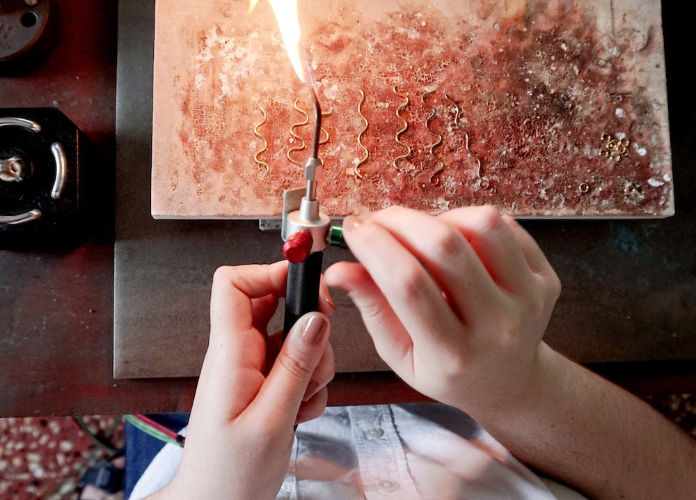 Aleishla uses a blow torch to solder her pieces together.