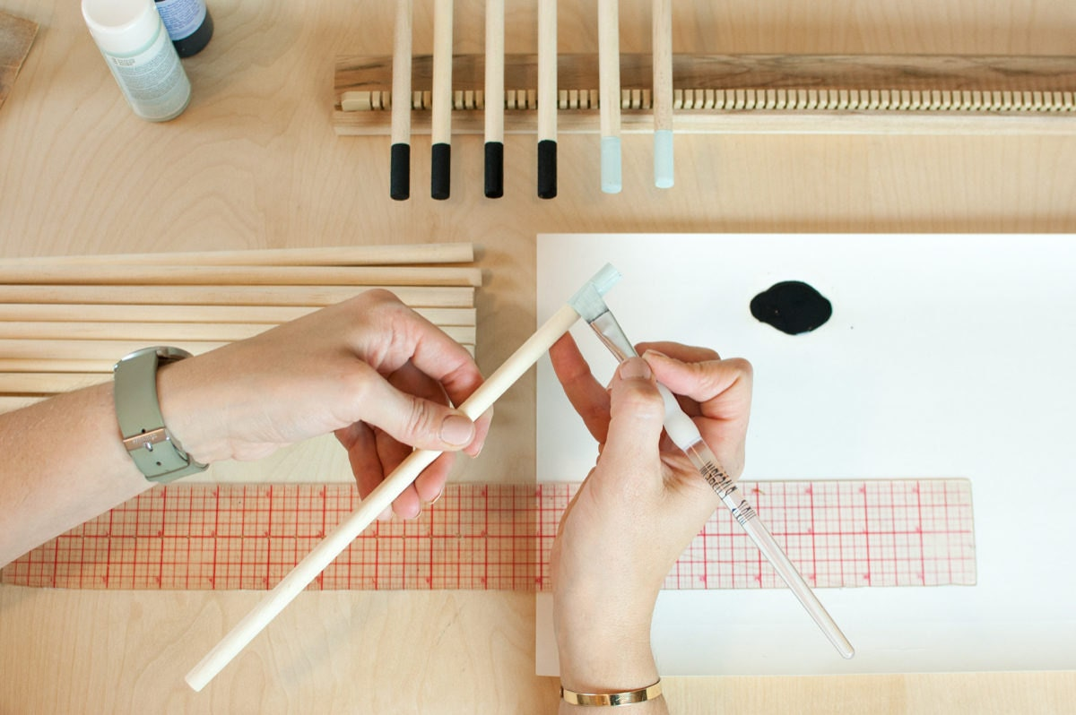 Ashley paints the tips of wooden dowels that will be come hanging rods for her loom kits.