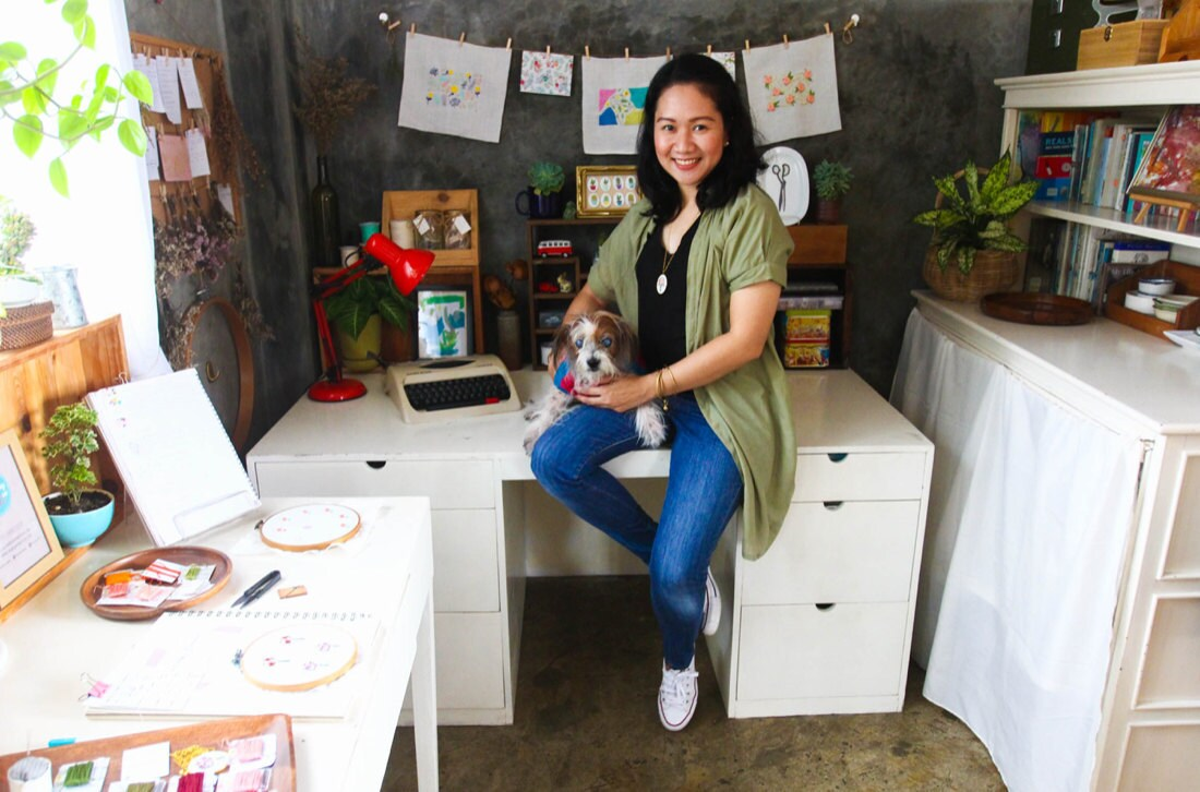 Portrait of Ruby Thursday More in her workspace, holding one of her pet pups
