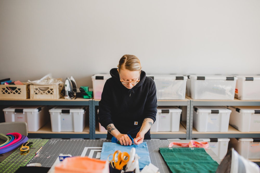 Hanna sews a strap onto a market bag in her sewing studio.