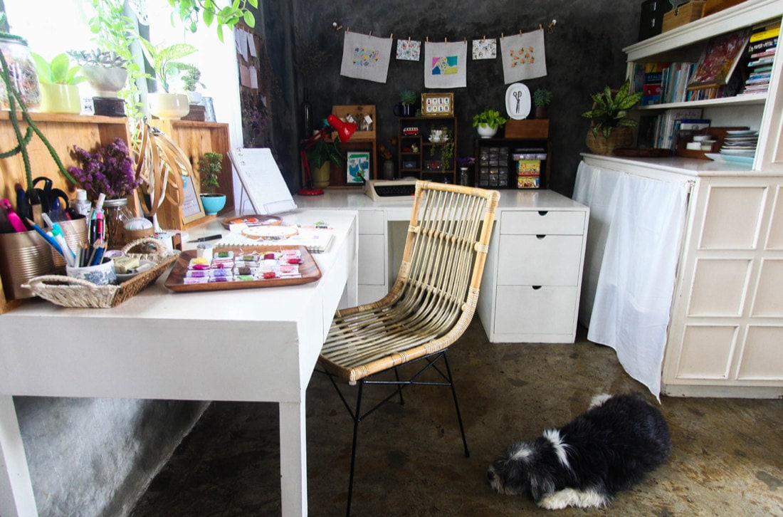A pup lies at the foot of Ruby's work space, which is full of colorful artwork, crafting books, and embroidery supplies