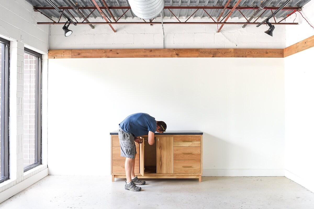George adjusts the hardware on a vanity